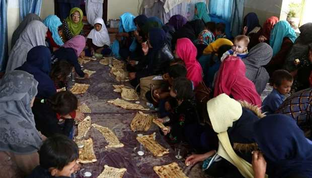Internally displaced Afghans eat breakfast after arriving from Jaghori district of Ghazni fleeing on