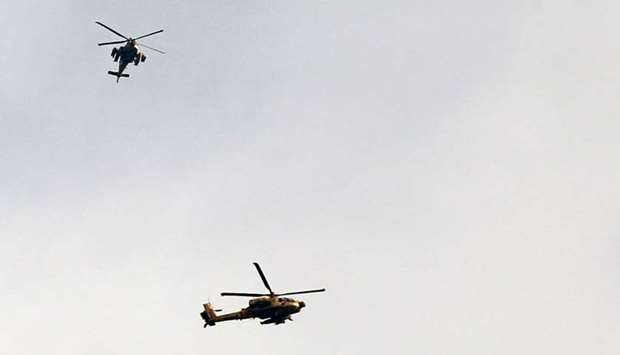 Israeli Apache helicopters fly over the border between Israel and the Gaza Strip