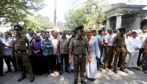 Sri Lanka's police officers stand guard as supporters wait outside the court for a decision after de