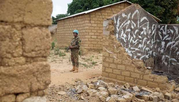A United Nations peacekeeping soldier stands among houses destroyed by violence, in the abandoned vi