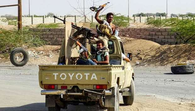 Yemeni pro-government forces cheer as they ride in the back of a pickup truck mounted with a machine