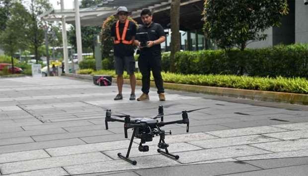 Staff members of Singapore technology firm H3 Dynamics preparing to fly a drone to inspect a buildin