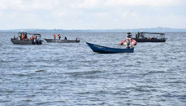 Local fishermen and Ugandan Navy personnel search passengers of capsized  boat on lake Victoria at M