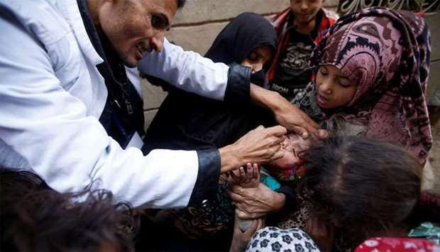 Children gather around a girl receiving a polio vaccination during a house-to-house polio immunisati