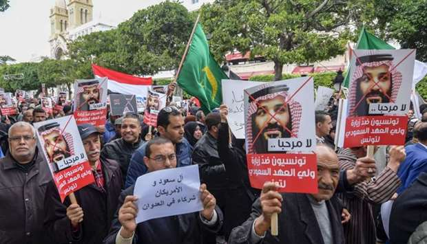 Tunisians shout slogans and hold up signs as they protest against the visit of the Saudi Crown Princ
