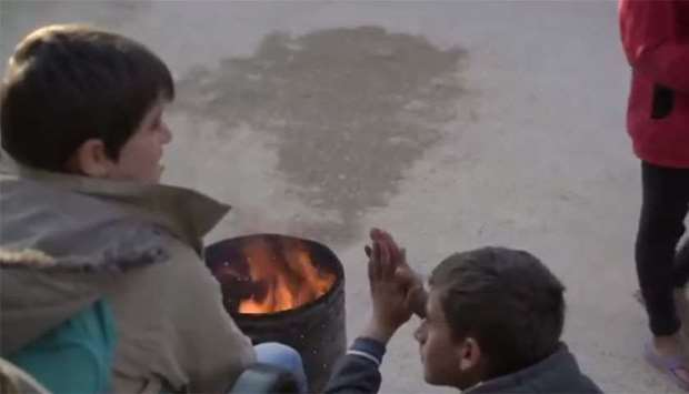 Palestine children try to keep themselves warm by lighting a fire.