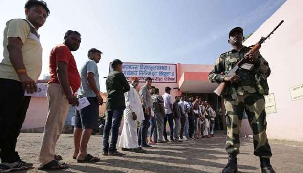 A security official stands guard as voters queue outside a polling station to vote in India's Madhya