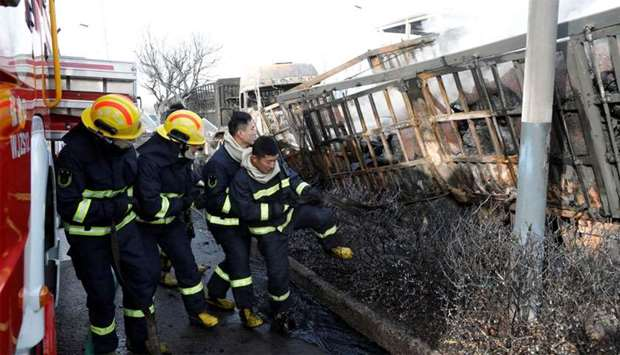 Firefighters work next to burnt vehicles following a blast near a chemical plant in Zhangjiakou