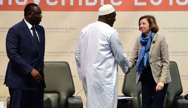Gambia's President Adam Barrow (C) shakes hands with French Defence Minister Florence Parly (R) as t