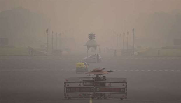 Commuters are seen amid heavy smog in New Delhi