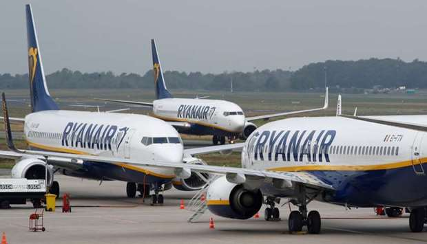 A Ryanair airplane taxis past two parked aircraft at Weeze Airport, near the German-Dutch border, du