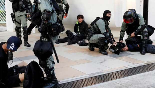 Protesters are detained by riot police officers during an anti-government demonstration in Hong Kong