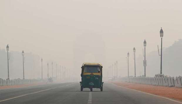 An auto-rickshaw moves past the India Gate on a smoggy morning in New Delhi