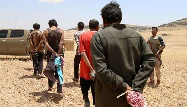 Men, who the Democratic Forces of Syria fighters claimed were Islamic State fighters, walk as they a