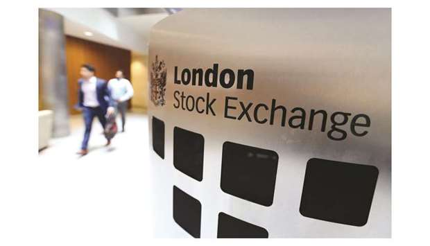 Visitors pass a sign inside the London Stock Exchange Group headquarters. The FTSE 100 index closed