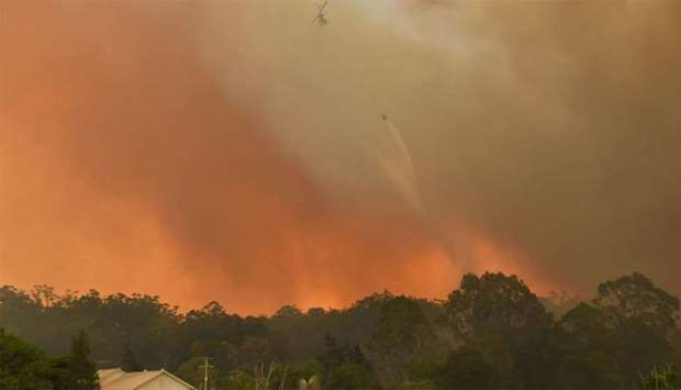 A helicopter drops water on a homestead as bushfires impact on farmland near the small town of Nana