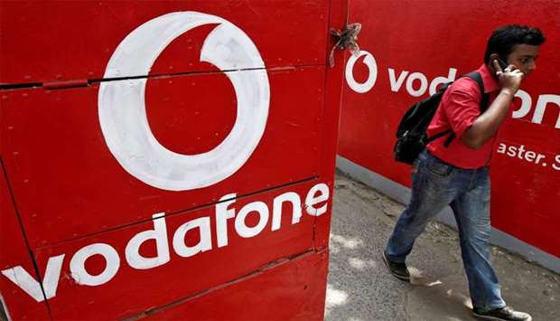 Man speaks on his mobile phone as he walks past the logos of Vodafone painted on a roadside wall in