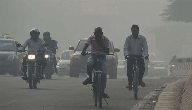 Drivers and cyclists make their way along a road under heavy smog conditions in New Delhi