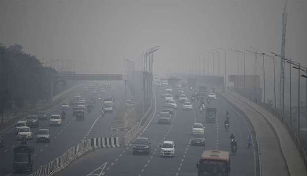 Commuters drive along a motorway under heavy smog conditions in New Delhi