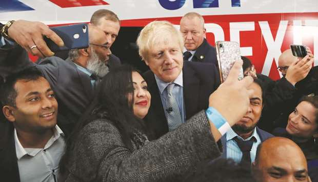 Prime Minister Boris Johnson poses for a picture with a supporter in front of the general election c