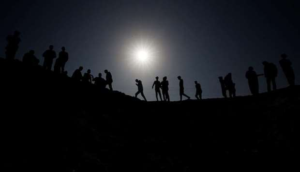 Palestinians gather at the scene of an Israeli air strike in the central Gaza Strip on Nov 14