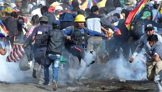 Coca growers, supporters of former President Evo Morales, run away from tear gas as one of them kick