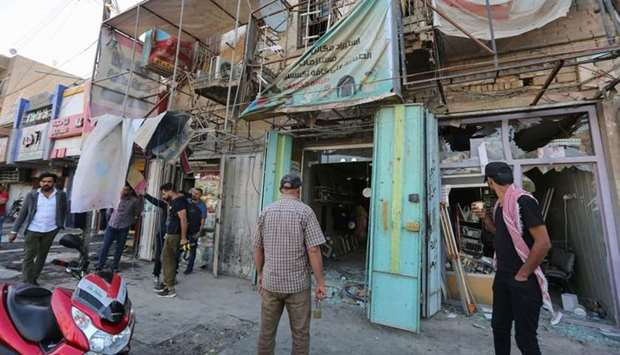 Iraqis stand at the site of a bomb explosion near Baghdad's Tahrir Square