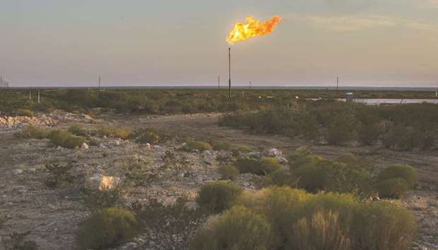 A gas flare burns at dusk in the Permian Basin in Texas. American oil production has more than doubl