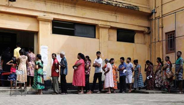 People stand in a line to cast their votes during the presidential election at polling station in Co