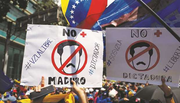 "People hold placards saying ""No more Maduro"" during a protest march against Venezuela's President Ni"