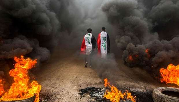 Anti-government protesters draped in Iraqi national flags walk into clouds of smoke from burning tir