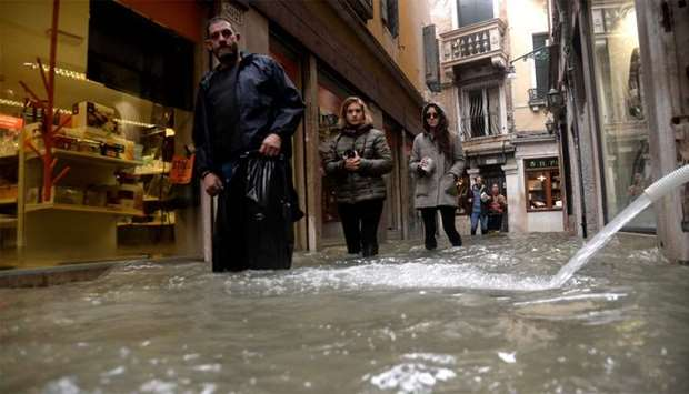 """People walks in flooded street as a pump hose spouts water from a shop in Venice, during """"acqua alta"""