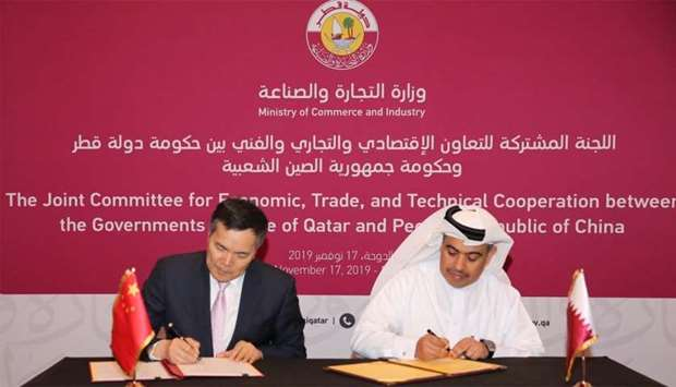 Al-Kuwari and Keming signing the minutes of the meeting.