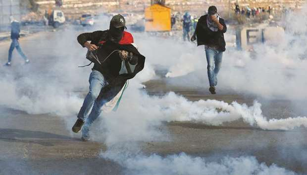 Palestinian demonstrators run away from tear gas fired by security forces during an anti-Israel prot