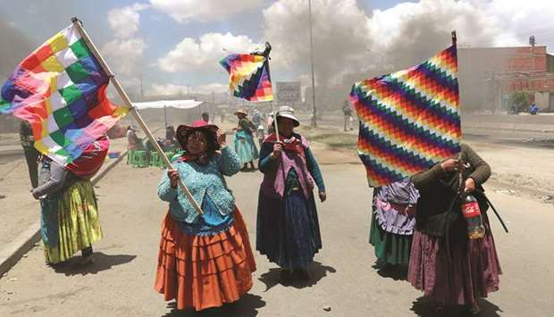 Supporters of the former president of Bolivia, Evo Morales, hold Wiphala flags during a protest in E