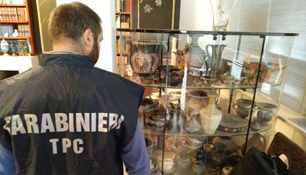 Carabinieri military policeman looks at artefacts in a display case in Cosenza, Italy