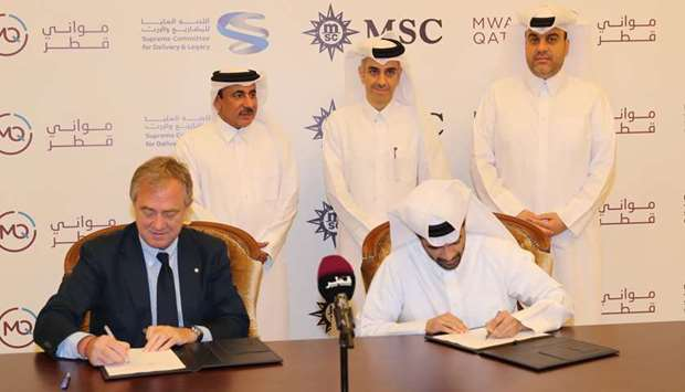 Hassan al-Thawadi and Pierfrancesco Vago signing the agreement as HE Jassim Seif Ahmed al-Sulaiti an