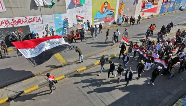 Iraqi youths waving national flags march through Tahrir Square in the Iraqi capital Baghdad as anti-