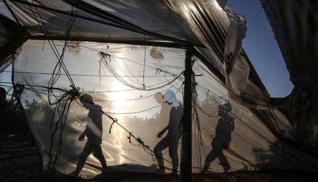 Palestinian men walk behind a greenhouse damaged by an Israeli airstrike launched in response to roc