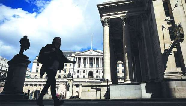 A pedestrian walks past the Bank of England in the City of London