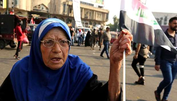An elderly Iraqi woman waves a national flag in the capital Baghdad's Tahrir square during ongoing a