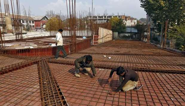 Migrant workers fasten iron rods together at the construction site of a parking lot in Srinagar Octo