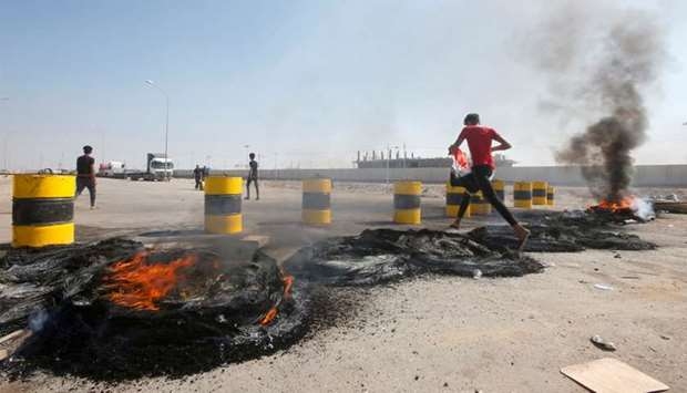 Iraqi protesters burn tires as they block the entrance of Umm Qasr Port south of Basra, Iraq