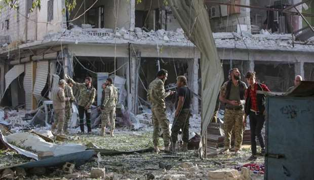 Turkey-backed Syrian fighters inspect the site of a car bomb explosion in the northern Syrian Kurdis