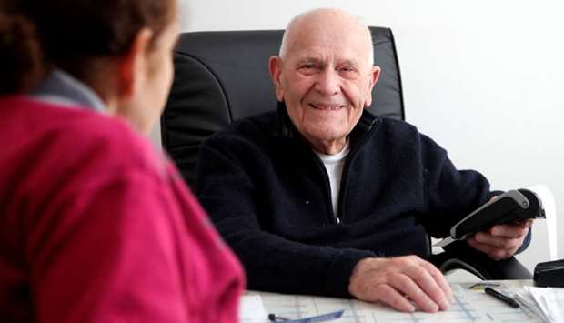 French doctor Christian Chenay, 98 years-old, treats a patient in his consulting room in Chevilly-La