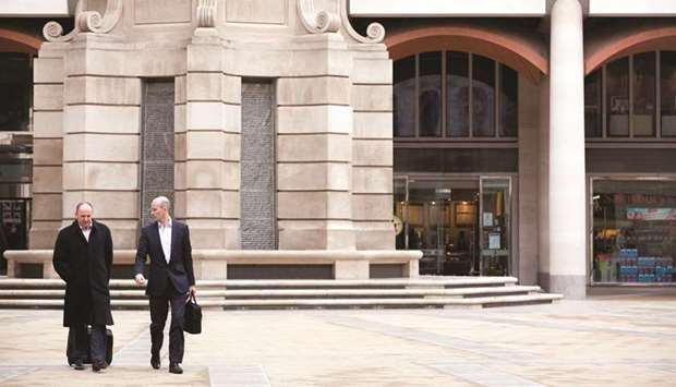 Pedestrians walk across Paternoster Square in front of the London Stock Exchange Group headquarters.