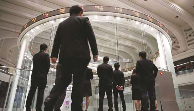 Visitors watch share prices at the Tokyo Stock Exchange. The Nikkei 225 closed up 0.3% to 23,122.88