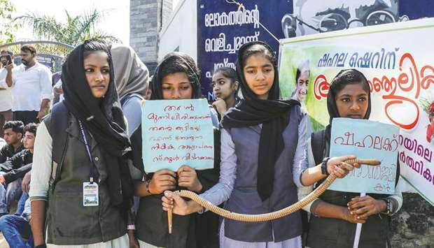Students hold placards and a toy snake during a protest yesterday over the death of a girl after she