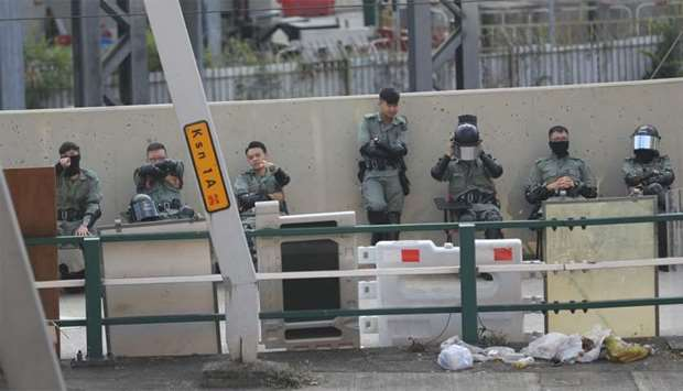 Police guard the perimeter of Hong Kong Polytechnic University (PolyU) in Hong Kong