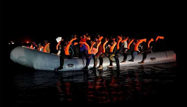 Migrants sit in a rubber boat before being rescued during a search and rescue operation by the NGO P
